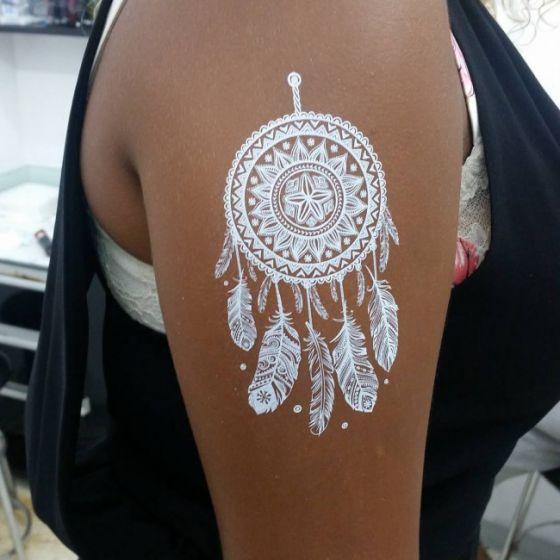 tatuaje blanco sobre piel morena